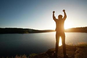 vandrare man vinnare siluett på bergstoppen. äventyrsliv. foto