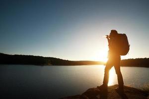 silhuett av vandrare mannen med ryggsäck i solnedgången landskap berg. foto