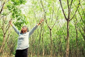 vacker ung kvinna njuter av naturen i skogen foto