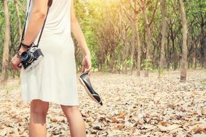 kvinnors händer som bär skor och retrokamera som går i skogen foto