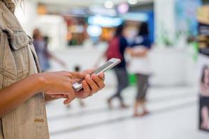 ung kvinna hand innehav skriva smartphone för att chatta på köpcentret. foto