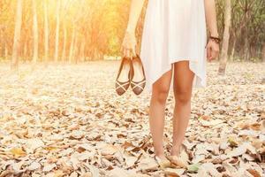 ung kvinna som bär skor när hon tröttnade på att gå i skogen foto