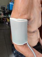 närbild asiatisk gubbe som mäter högt blodtryck foto