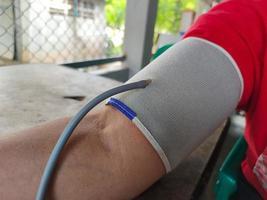 närbild asiatisk fet kvinna som mäter högt blodtryck foto