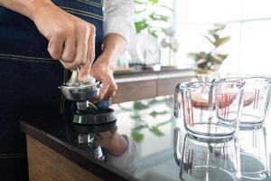 barista med kaffekvarnmaskin för att riva kaffebönor i caféet foto