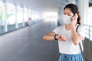 ung kvinna som bär mask med smartphone under pandemi foto