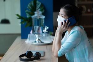 asiatisk kvinna med mask och hålla social distans på café foto