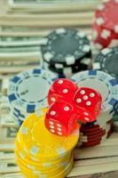 röda tärningar pengechips och spelkort foto