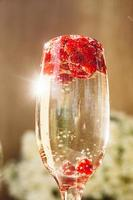 mousserande vin i glas med röda vinbär foto