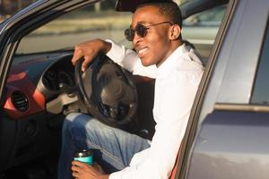 glad afroamerikan som kör bil, på sommaren foto