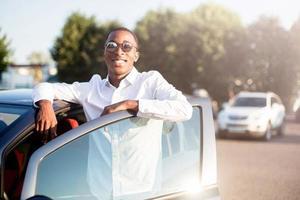 glad afrikansk amerikan bredvid en bil på sommaren foto