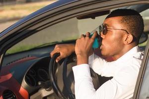 glad afroamerikan som kör bil med kaffe, på sommaren foto