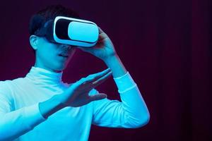 ung asiatisk man som bär virtual reality -glasögon som tittar på 360 -video foto