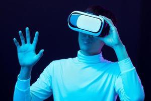 ung asiatisk man som bär virtual reality -glasögon och tittar på 360 graders vdo foto