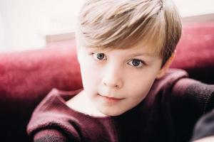 en närbild porträtt av en söt unge pojke med grå ögon foto
