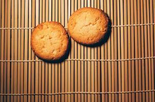 två runda krispiga kakor, på texturerad bambu, enkel design foto