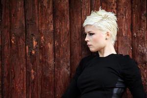 blond kvinna nära träväggen foto