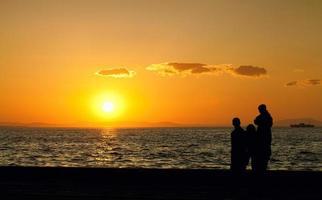 människor siluett och havet i solnedgången foto