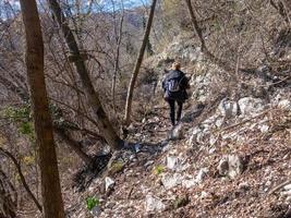 kvinna som går uppför med skandinaviska vandringsstavar i alperna foto