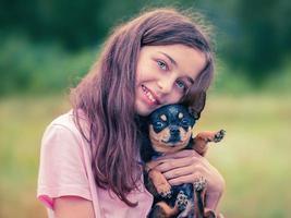 hund i famnen på en tonårsflicka. svart chihuahua. foto