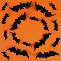 svarta fladdermöss på en orange bakgrund med kopieringsutrymme foto