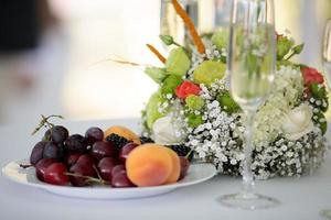 bröllopsdekoration på bordet. brudbukett och bär foto