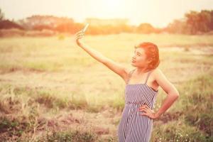 ung kvinna som använder sin smartphone -selfie i gräsfältet. foto