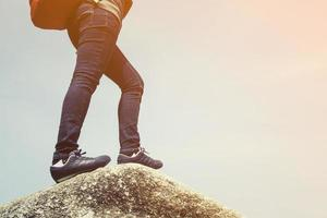 vandrare med ryggsäck stående på toppen av ett berg foto