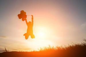 silhuett av ung kvinna hoppa innehav av ballonger med solnedgång. foto