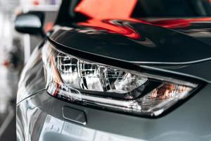 närbild av en strålkastare på en modern bil med reflektion. foto