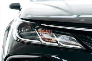 närbild av en strålkastare på en modern svart bil med reflektion. foto