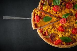 stor italiensk pizza med tomater och basilika på en svart bakgrund. foto