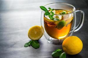 te med citron och mynta i transparent kopp foto