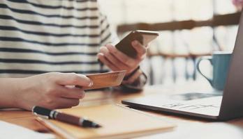 online betalning, kvinnans händer som håller smartphone och använder kreditkort foto