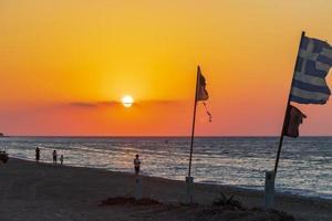 flaggor vid den vackraste solnedgången på Ialysos -stranden på Rhodos, Grekland foto