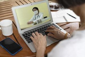 senior kvinna konsultera läkare via videosamtal foto