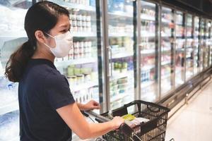 ung asiatisk kvinna som bär mask medan hon handlar mat i stormarknaden foto