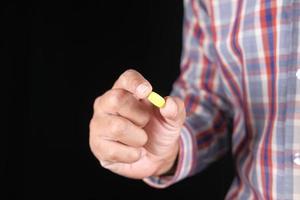 ung man som håller medicinska piller isolerade på svart foto