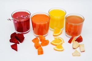 glasögon med juice och bitar av grönsaker och frukter foto