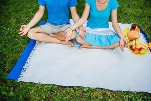 ungt par som sitter i en meditativ pose som kopplar av i naturen foto
