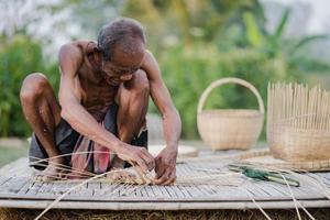 äldre man och bambu hantverk, livsstil för lokalbefolkningen i Thailand foto