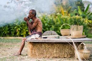 äldre man livsstil för lokalbefolkningen med hantverk bambu foto