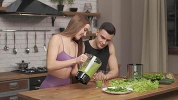 älskande par idrottare förbereder hälsosam drink, leende kvinna som häller detox smoothie i glas. njuta av tiden tillsammans, positiva känslor, må bra. hälsosamma vitaminer, kost, kost koncept. foto