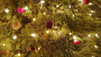 närbild ett julgransljus som glittrar på natten. nytt år gran med dekorationer och belysning. foto