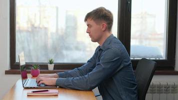 ung man frilansare använder bärbar dator, skriver, rullar, surfar på webben, tittar på skärmen. professionell kreativ millennial sitter vid sitt skrivbord i hemmakontorsstudio som arbetar 4k. foto
