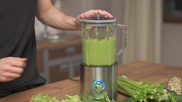 mannen slår på mixer med en färdig grön smoothie, för bättre blandning foto