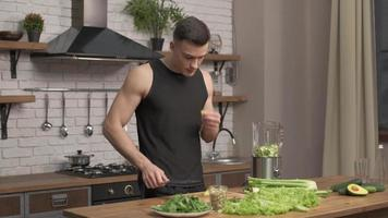 idrottsman man förbereder ingredienser för smoothie i ett modernt kök. beredning av grönsaker för detox i mixer. avokado, selleri, gurka i flytande silverpott i bakgrunden. full HD foto
