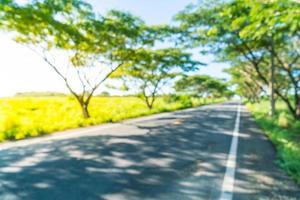 abstrakt oskärpa asfaltvägen i skogen - öka färgbehandlingsstil med solbländande effekt foto
