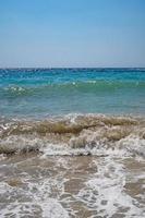 klart hav och vågor på stranden på sommaren foto