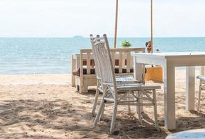 vita stolar och bord på stranden med utsikt över det blå havet foto